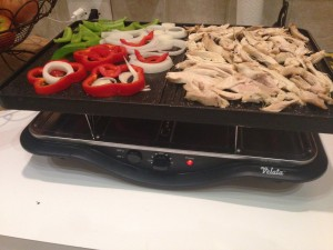 pulled chicken getting toasty with peppers and onions on the raclette