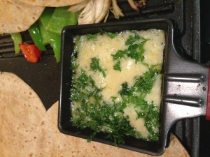cheese and parsley combining in the raclette pan