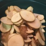 Sliced russet potatoes in a casserole dish.