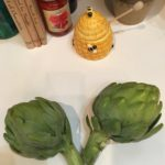 Pair of artichokes on countertop.