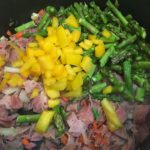Bell pepper and asparagus in a saute pan with ham and onion.