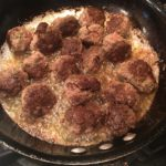 Meatballs browning in oil in a saute pan.
