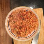 Short pasta in bowl with tomato sauce.