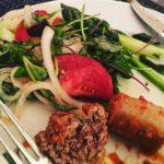 Meatballs, sausage and salad on a plate.